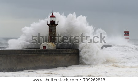 waves-crashing-over-lighthouse-450w-789262813.jpg